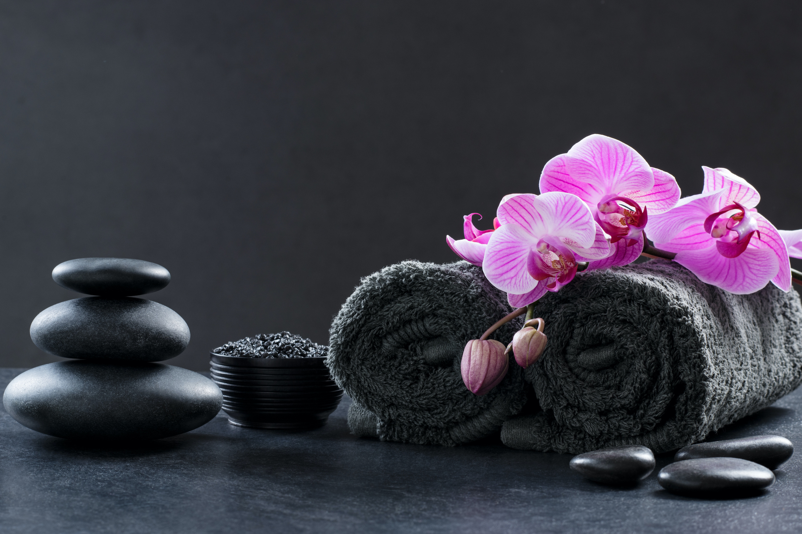 Black spa setting with grey towels, hot stones and beautiful orchids. Spa and wellness background with stack of hot stones with pink flowers on blackboard. Luxury spa composition and relax concept.